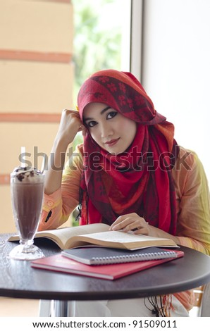 beautiful young muslim woman with lovely smiles reading and having lunch at coffee shop - stock photo