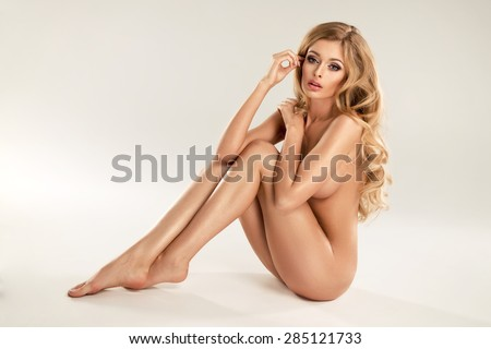 Beautiful young naked blonde woman sitting over the background - stock photo