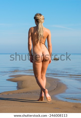 Beautiful young naked woman posing on the beach. Enjoying summer time near the sea - stock photo