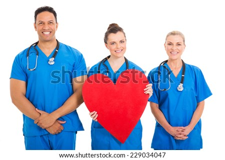 beautiful young nurse holding heart shape with colleagues - stock photo