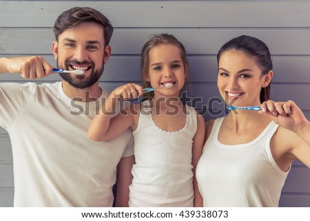Beautiful young parents and their cute little daughter are looking at camera and smiling while brushing teeth, against gray wall - stock photo