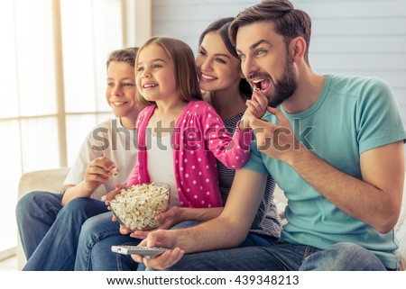 Beautiful young parents, their  daughter and son are watching TV, eating popcorn and smiling, sitting on sofa at home. Dad is using a remote control - stock photo