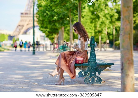 Beautiful young Parisian woman in long skirt near the Eiffel tower on a summer day, sitting on the bench and using mobile phone - stock photo