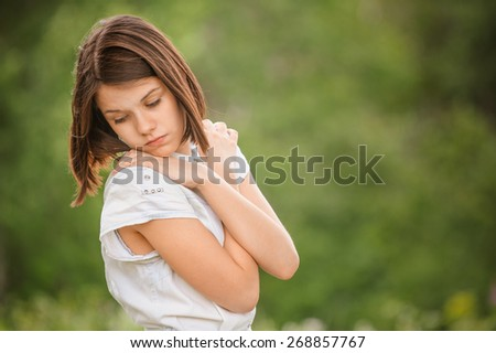 Beautiful young pensive woman standing with hands folded against at summer green park - stock photo