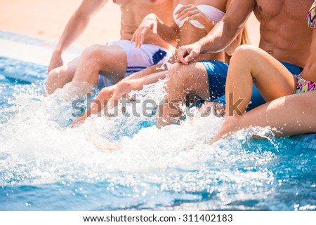 Beautiful young people having fun in swimming pool. Close-up. - stock photo