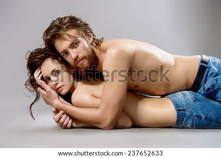 Beautiful young people in love. Studio shot. Jeans style. - stock photo