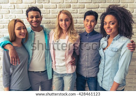 Beautiful young people of different nationalities are looking at camera and smiling, standing against white brick wall - stock photo