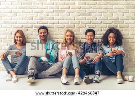 Beautiful young people of different nationalities are using gadgets, looking at camera and smiling, sitting against white brick wall - stock photo