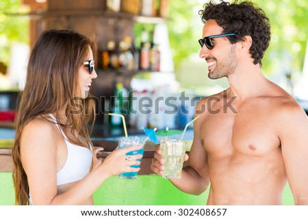 Beautiful young people talking in a beach bar - stock photo
