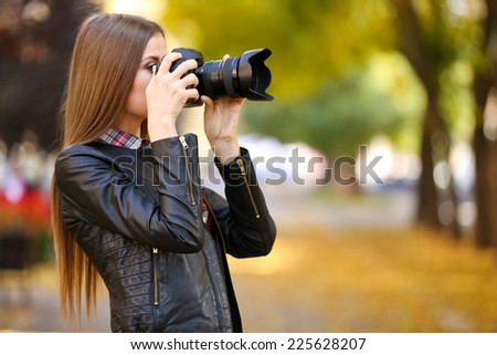 Beautiful young photography take photos outdoors in park - stock photo