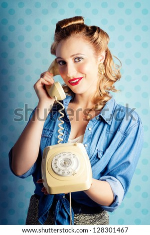 Beautiful Young Pin-Up Woman With Sixties Era Make-Up And Classical Hairstyle Posing With Retro Telephone While In Gossip Converse - stock photo