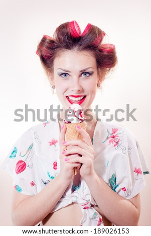 Beautiful young pinup woman eating ice cream cone looking in camera isolated on white background - stock photo
