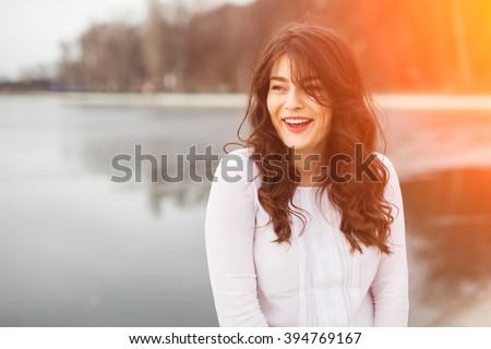 Beautiful young plus size woman wearing white blouse laughing near lake with copy space and lens flare effect - stock photo