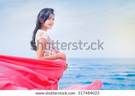 beautiful young pregnant asian woman on a beach - stock photo