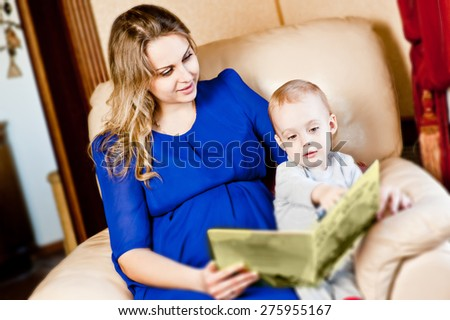 Beautiful young pregnant woman and her son are reading a book while sitting on the couch. - stock photo