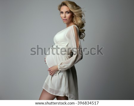 Beautiful young pregnant woman posing in studio in dress. Girl looking at camera. Expecting woman. - stock photo