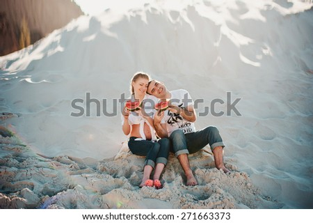 Beautiful young pregnant woman with her husband sitting on the beach and eating watermelon, laughing - stock photo