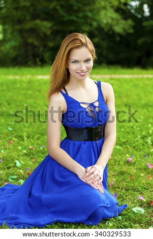 Beautiful young red-hair woman in blue dress, against green of summer park  - stock photo