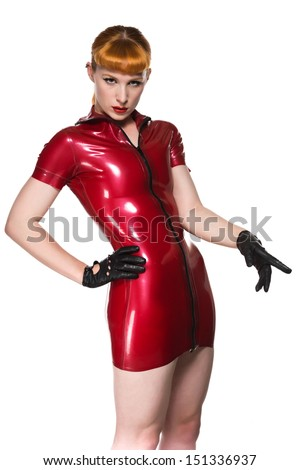 Beautiful young redhead in a red latex dress - stock photo