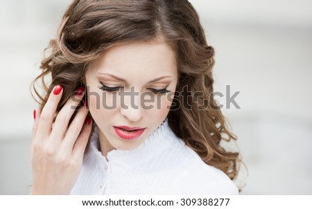 Beautiful young romantic elegant woman face, has closed eyes, haired nature hair, long eyelashes, hand with red manicure, sexy lips. Pure makeup. White blouse.  Studio. Hairstyle. Lipstick nature - stock photo