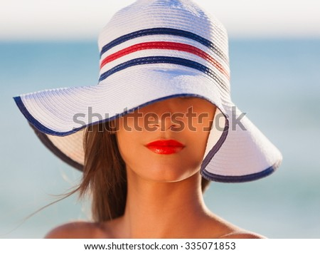 Beautiful young romantic elegant woman face, has happy fun cheerful smiling face, brunette nature hair, sexy red lips, tan skin, white hat . Pure makeup. Sea background.  - stock photo