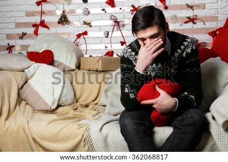 Beautiful young sad lonely man sitting on the bed hugging a pillow in the shape of heart, symbolizing the loneliness on Valentine's Day - stock photo