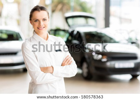 beautiful young sales consultant working in car showroom - stock photo