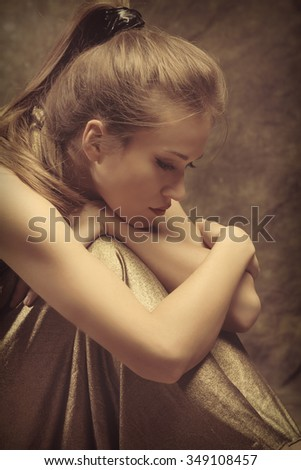 beautiful young sensual woman in golden dress sit with wrap  arms around legs, side view, studio shot - stock photo