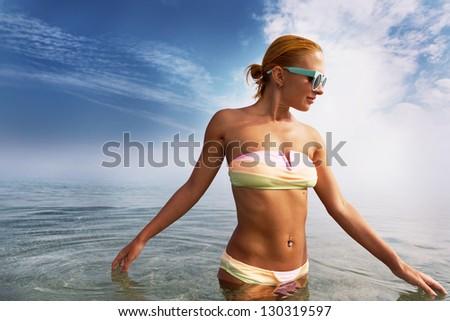 Beautiful young sensuous woman wearing bikini in the sea - stock photo