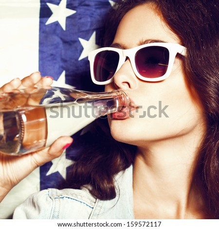 Beautiful young sexual woman in sunglasses with national usa flag in background drinking water. Lifestyle - stock photo