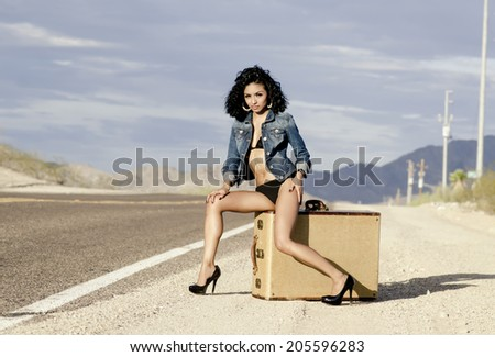 Beautiful young sexy exotic woman long legs sitting on luggage suitcase wearing bikini and denim jacket on a lonely desert road in the USA. - stock photo