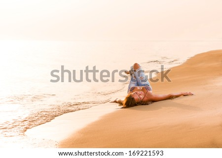 Beautiful young sexy fashion model in jeans by the sea at sunrise - stock photo