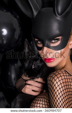beautiful young sexy model in a black carnival mask, rabbit ears, holding the hands of a living rabbit witht the black balloons and sensually looks at the camera, wearing a bodystocking with mesh - stock photo