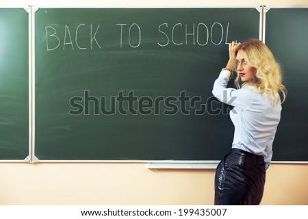 Beautiful young sexy teacher standing near the blackboard - stock photo