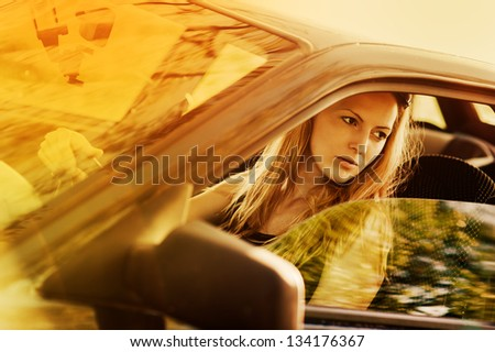 Beautiful young sexy woman in car looking from window on nature background - stock photo