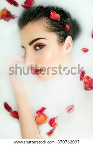Beautiful young sexy woman with dark hair wet and makeup in milk bath. Wellness  and SPA. Romantic atmosphere for woman at Valentine's Day. Selective focus. Copyspace. - stock photo