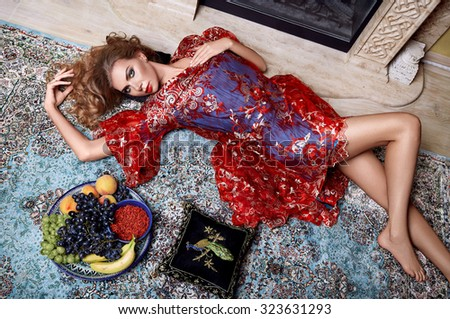 Beautiful young sexy woman with long hair blond and decoration in evening dress of silk lace, room bedroom  velvet pillows luxurious furniture fashion bed perfect body shape fruit vitamin makeup skin - stock photo