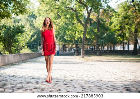 Beautiful young slim woman in a street of European city, business lady in red dress and high heels, walking in park. - stock photo