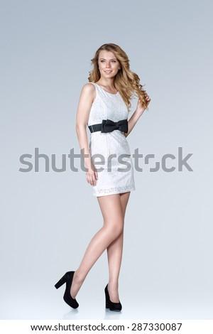 Beautiful young slim woman in white mini dress full body studio portrait - stock photo