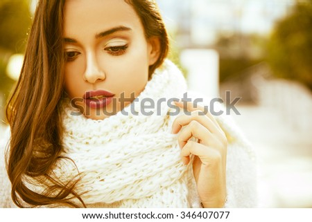 Beautiful  young smiling brunette woman wearing knitted sweater and scarf. Fall and winter fashion concept. Bokeh background. Outdoors shot. Horizontal - stock photo