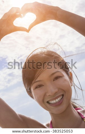Beautiful young smiling Chinese Asian woman girl on a beach in a bikini, making a hand heart shaped finger frame  - stock photo