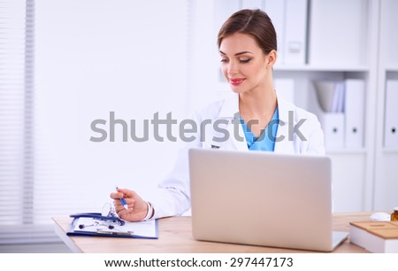 Beautiful young smiling female doctor sitting at the desk  - stock photo