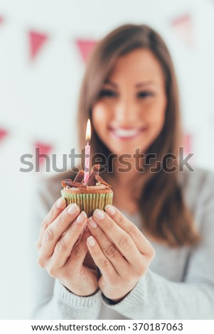 Beautiful young smiling woman holding small birthday cake with candle. Selective focus. Focus on cupcake, on foreground. - stock photo