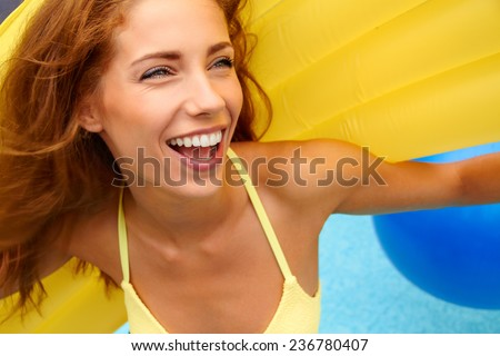 Beautiful young smiling woman in the pool  - stock photo
