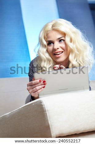 Beautiful young smiling woman with laptop on the sofa - indoors.  - stock photo