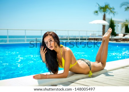 Beautiful young smiling woman with long hair in a bathing suit on the beach. Clean skin. - stock photo