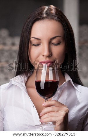 Beautiful young sommelier is examining the quality of red wine. She is holding wineglass and smelling it with pleasure. The woman is smiling. She is standing in cellar - stock photo