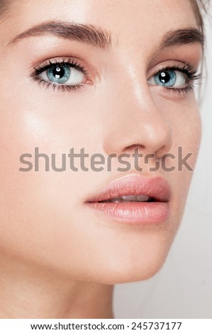 Beautiful young spa woman. Attractive girl Face with perfect Clean Fresh Skin close up. Beauty model. Blue eyed Lady. Youth and Skin Care Concept  - stock photo