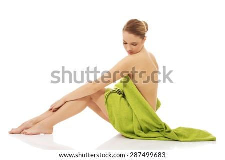 Beautiful young spa woman sitting wrapped with a towel. - stock photo