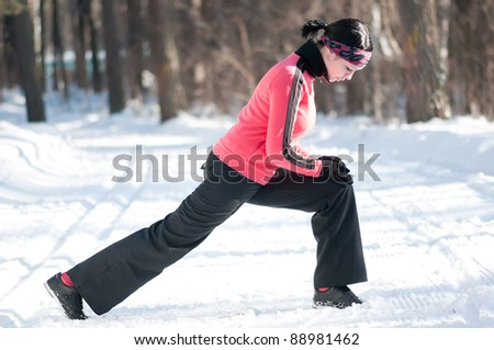 Beautiful young sport woman doing stretching fitness exercise in winter forest - stock photo